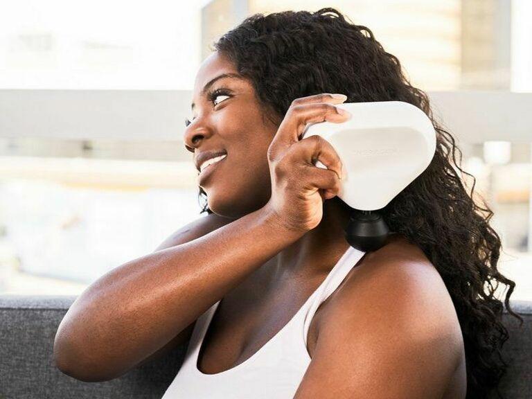 person smiling using white Theragun mini massaging device