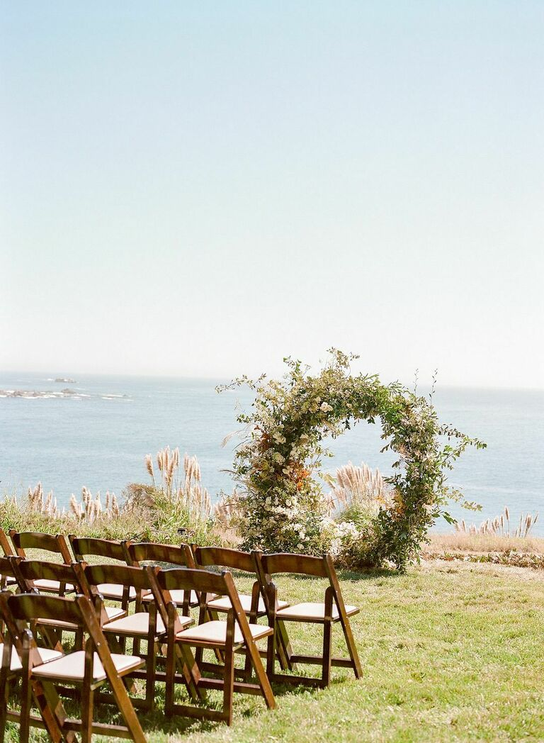 Waterfront wedding ceremony with wood folding chairs and greenery full-circle arch