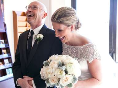 A bride and her father laughing just before the wedding ceremony