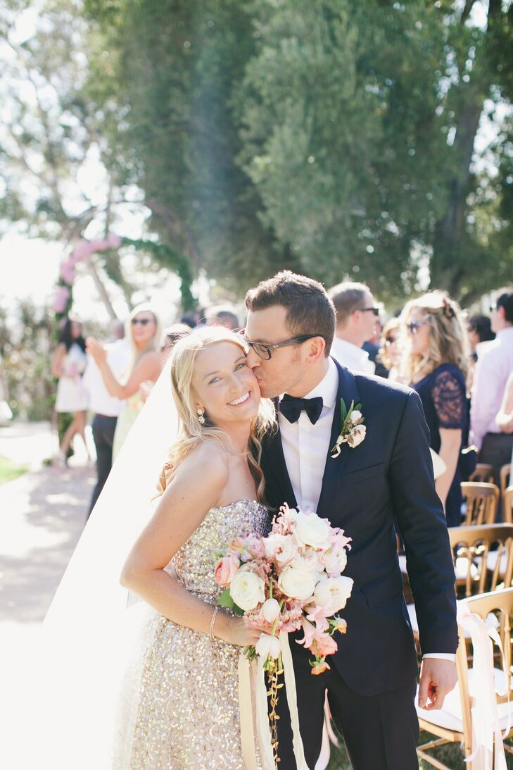 """Matt kissed Audrey on the cheek as they walked up the aisle during their recessional. """"Matt wore a navy blue Hugo Boss suit and bow tie to stand out among his groomsmen, who wore Zara gray suits with ivory ties,"""" Audrey says."""