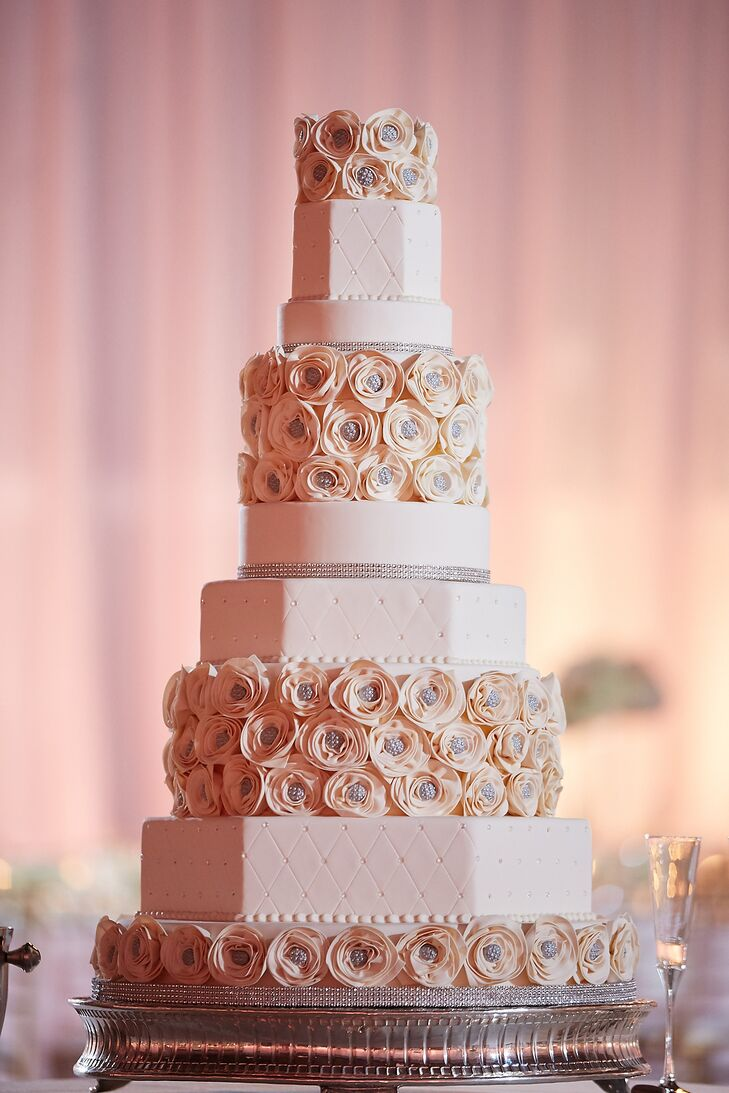 Maria and Chris enjoyed a nine-tier geometric ivory wedding cake for dessert. Three layers were adorned with geometric diamond patterns and crystals, two layers were round with crystal detailing on the bottom, and four layers were decorated with cream and crystal rosettes.