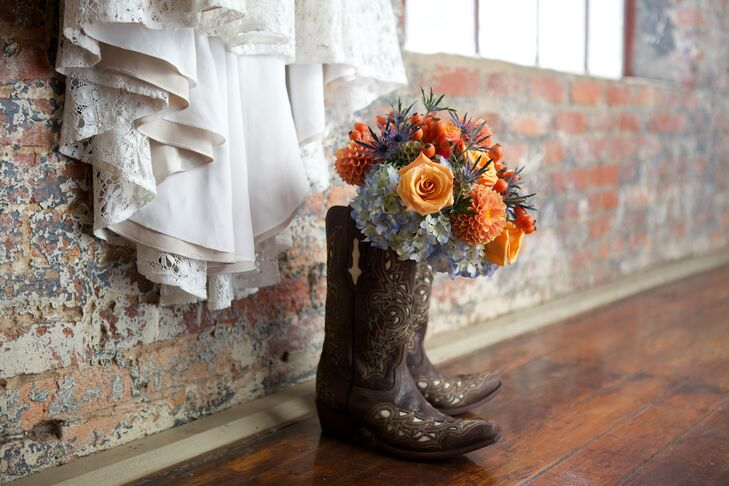 Nicole paired her cowboy boots with a brighter detail that fit the fall wedding. Bright orange roses, chrysanthemums and hypericum were arranged with blue sea holly thistles, scabiosa pods and blue hydrangeas in her bouquet. A burlap wrap tied it to the rustic theme.