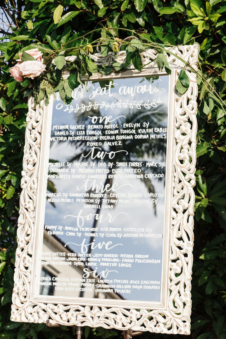 A calligraphed, white-framed seating chart shared guests' assigned tables.