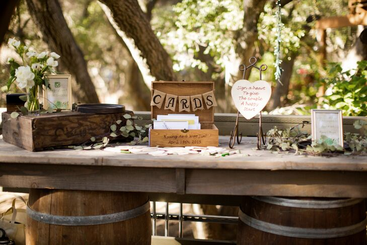"Placed outside the ceremony site and near the reception area was a wooden box marked with a hanging letter sign for guests to leave cards. Guests were also encouraged to ""sign a heart"" for Woo Jin and Kyung."