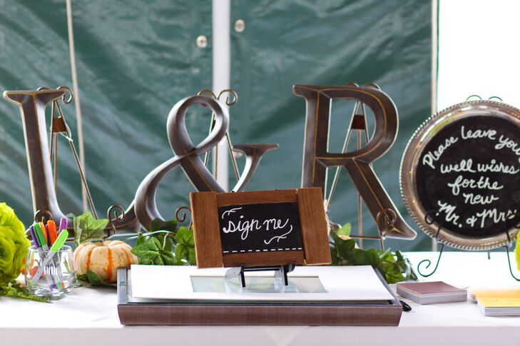Leslie used some of her vintage market finds to decorate the guest book table. Antique silver platters and wood-framed chalk boards were used as signs, encouraging guests to leave their well wishes for the newlyweds, while reclaimed metal lettering — an L and an R representing the couple's first names — was added for a personalized backdrop.