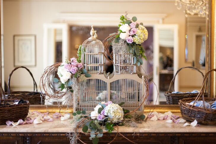 Emma took to her research from Pinterest and designed an accent for the yarmulke display that was entirely vintage. She covered a large silver birdcage with vines, purple and white roses and white hydrangeas. For the black and blue yarmulkes themselves, she put them in matching woven baskets on both sides of the cage.