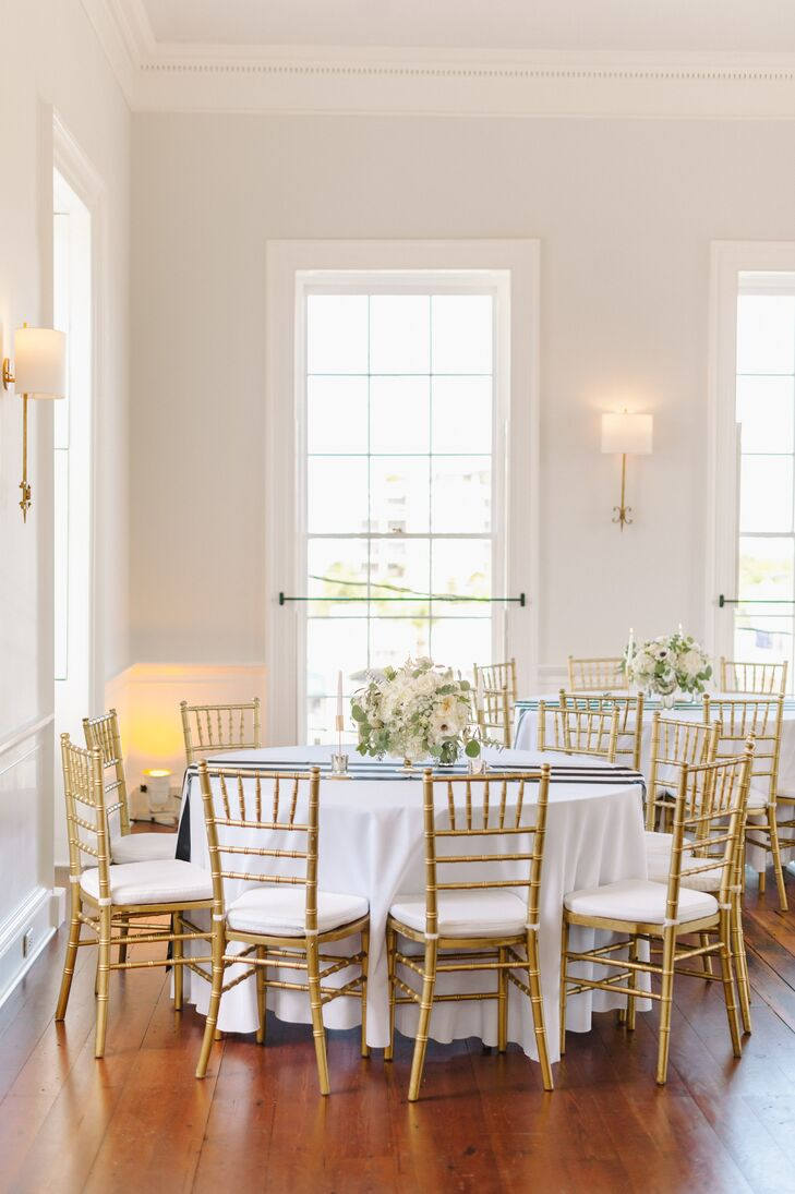 """Dining tables were cloaked in elegant white linens and black-and-white-striped runners and then topped with arrangements of white blooms and greenery. """"The decor on the tables created this beautiful glow during dinner, and I love that the centerpieces weren't too long so people could still communicate across the table,"""" Jennifer says."""