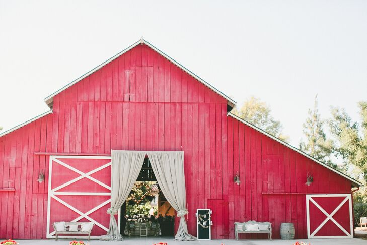 The classic red barn at Camarillo Ranch housed the reception, where guests entered through the open doorway draped with gray linens. The barn, Victorian house and beautiful open property won over Victoria and Robert when they first visited the venue.