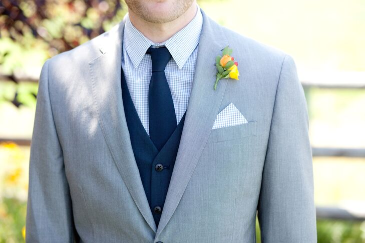 Kris rocked a light gray suit on the day of the wedding, paired with a white-and-blue-checkered pocket square that matched his collared dress shirt. He also wore a navy blue vest and tie to complete the outfit, embodying the two wedding day colors.