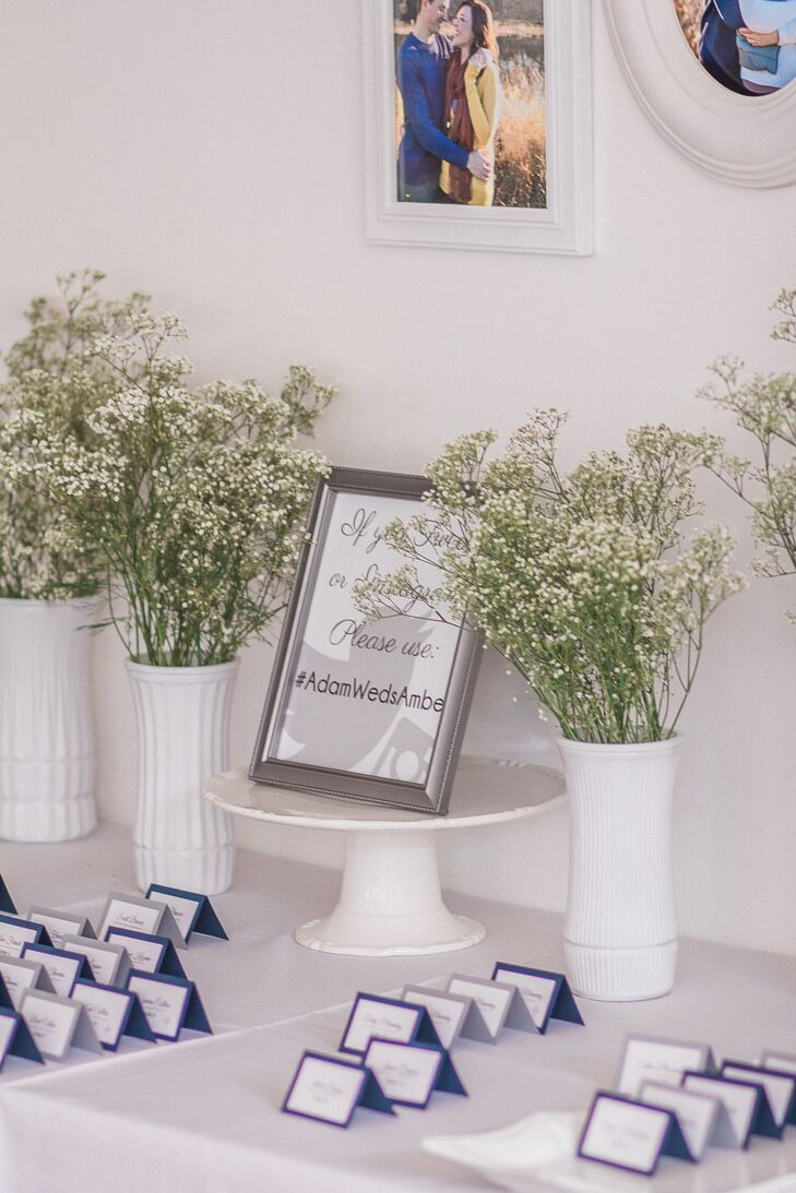 Amber and Adam used card stock to create their simple, blue- and silver-lined escort cards. The couple displayed their wedding hashtag between white vases of baby's breath.