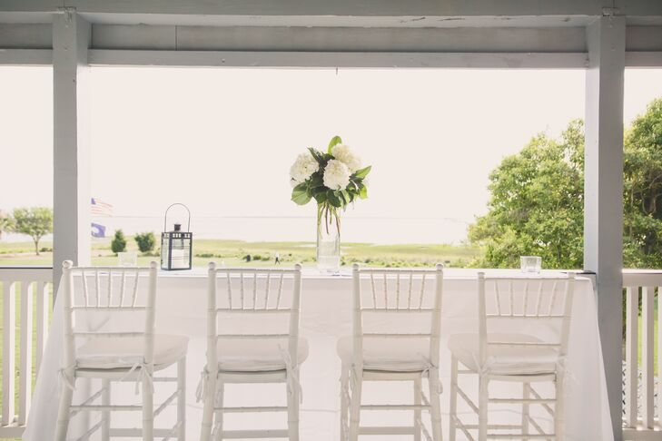 Alhambra Hall was the perfect location for Jenna and Joshua's lowcountry wedding because of its beautiful waterfront views. During cocktail hour, guests could enjoy these views on the patio, which was equipped with white cocktail tables and chiavari chairs. Flower arrangements of white hydrangeas and leafy greens decorated the outdoor area.