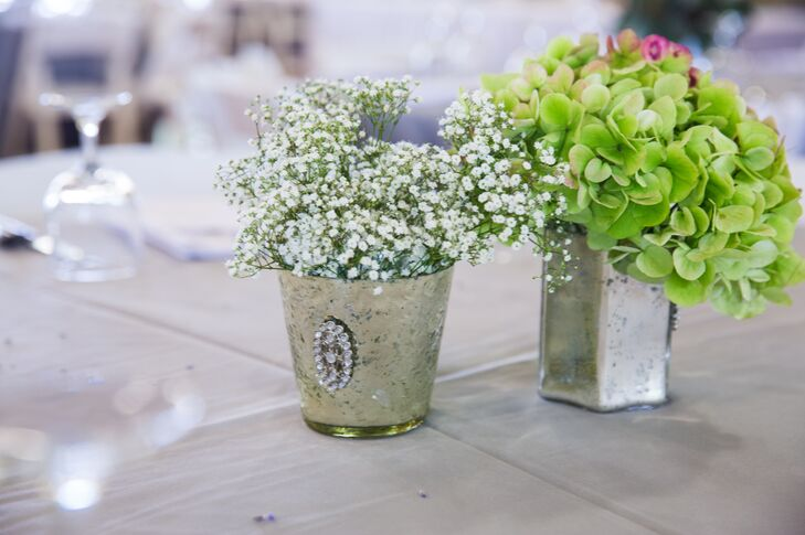 Small pails held lush, romantic arrangements of baby's breath and green hydrangeas for the centerpiece decor.