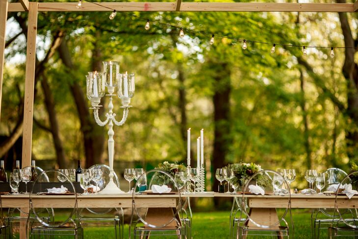 Elegant white candelabras and clear dining chairs were offset by industrial details, like place cards set in metal springs and oil cans. String lights, candle sticks, and hanging lanterns gave the wedding a warm romantic glow as the sun set behind the farmhouse.