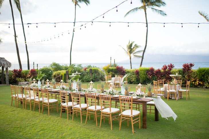 Bethany and Leonard hosted 20 guests at their outdoor reception at the Four Seasons Resort Maui in Wailea, Hawaii. A long banquet table was set with pineapples and banana leaves calligraphed in gold with the night's menu.