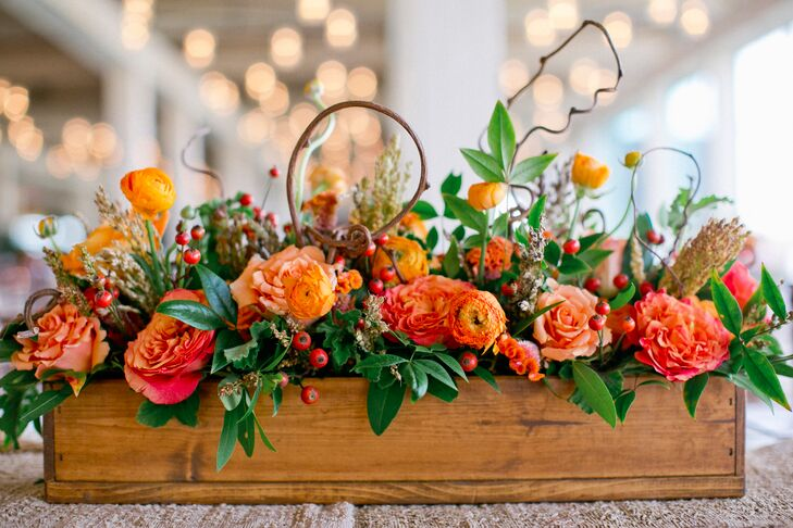 Tables were topped with arrangements of orange blooms and greenery that were displayed in rustic wooden boxes.