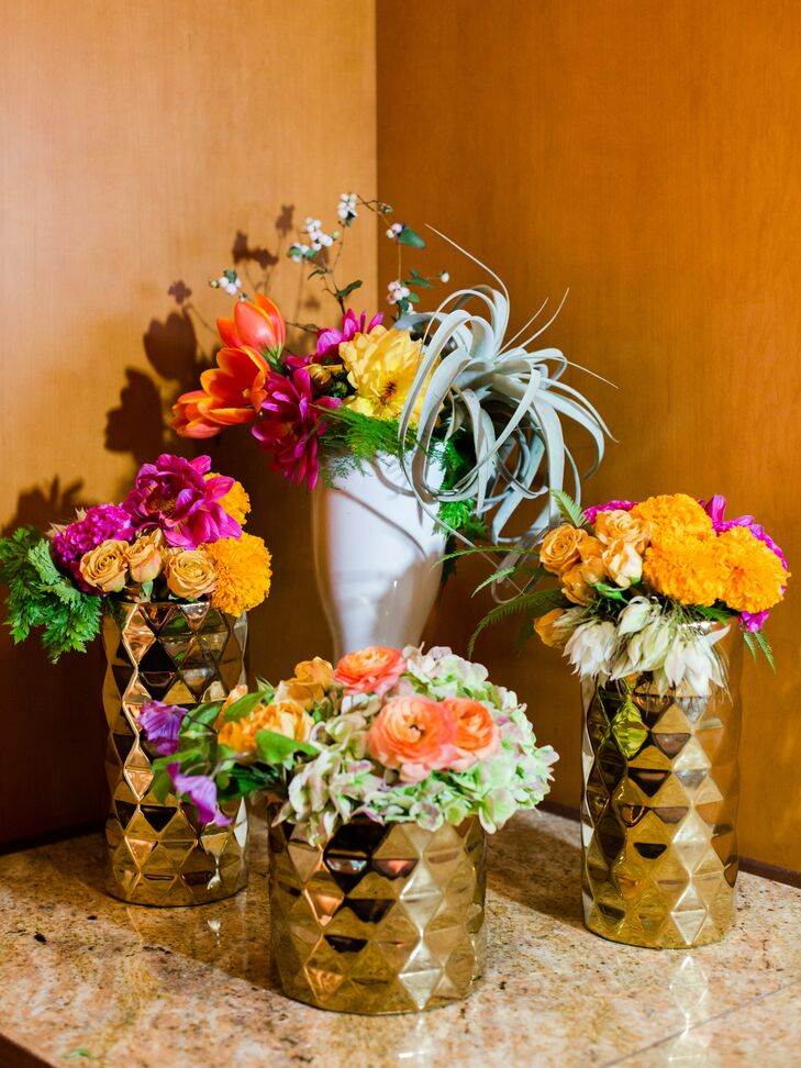 Arrangements of ranunculus, dahlias, roses, succulents and air plants in geometric gold vases were scattered throughout the reception space.
