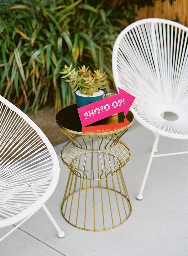 Metal table with pink acrylic photo booth sign sitting on top
