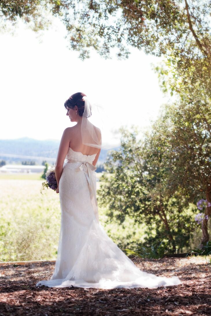 Jen's dress was elegant and romantic with delicate lace and a satin crystal-embellished ribbon. The elbow-length veil added a traditional touch to her look.