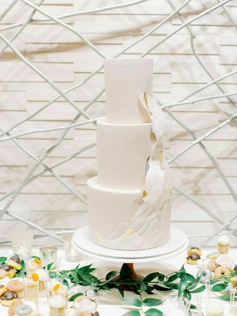 Modern white three-tier cake with wave-inspired decoration