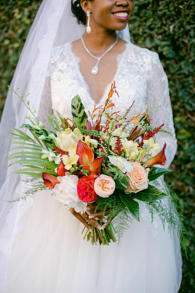 Bride holding tropical bouquet with greenery and orange blooms