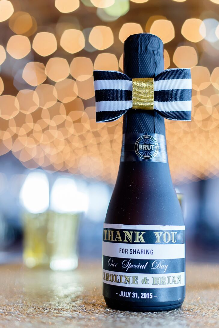 Caroline and Brian gave adorable miniature bottles of champagne to their guests. Each bottle marked the date of the wedding and was wrapped in an elegant black-and-white-striped bow that matched the Kate Spade–inspired reception decor.