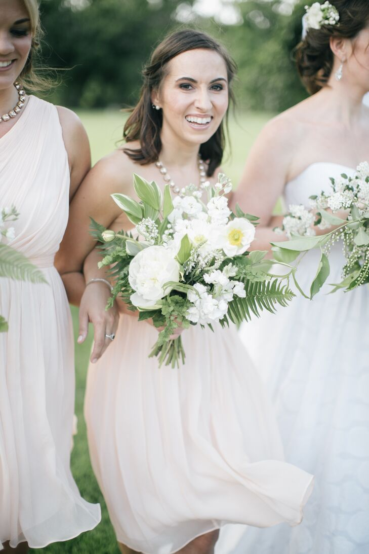 Bridesmaids wore pale peach J.Crew dresses with bauble necklaces and a pared-down version of Casey's bouquet, still featuring peonies, ranunculus, stock, Queen Anne's lace and greenery.