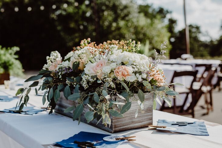 Emily's father handcrafted the flower boxes on the reception dining tables, which were filled with peach and ivory blossoms and leafy greenery.