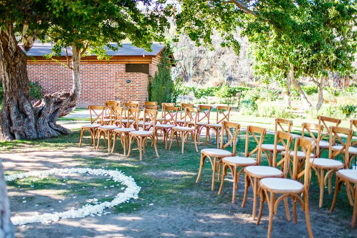 For Taylor and Cody's relaxed outdoor ceremony, cross-back chairs were arranged in a semicircle and petals were sprinkled at the altar.