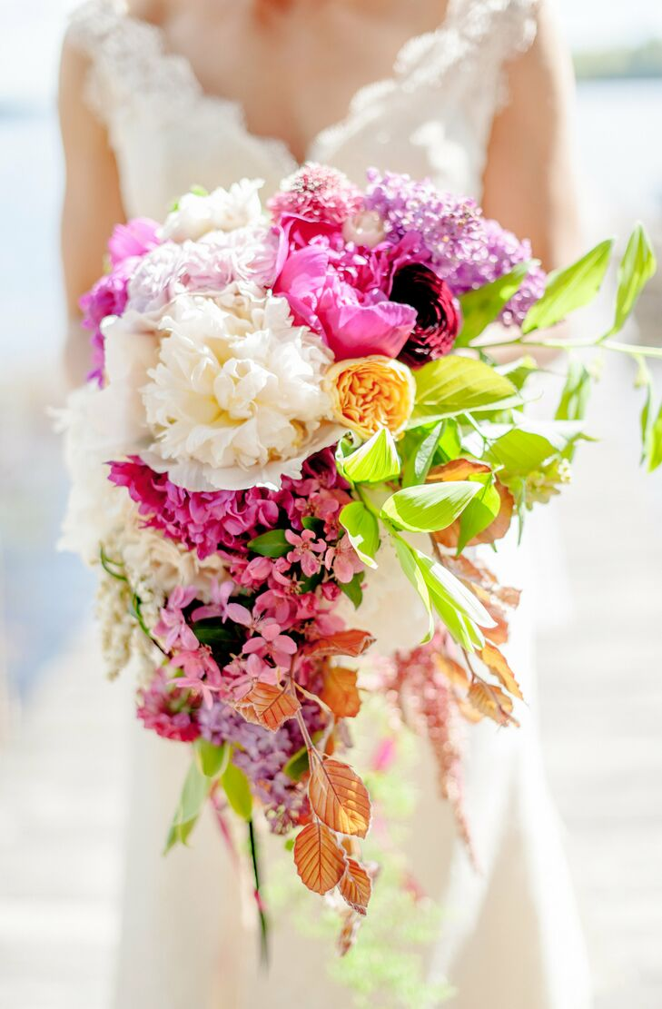 Petal Floral Design illuminated the day with vibrant arrangements of seasonal blooms. Michelle's bouquet overflowed with fresh, fragrant flowers like lilacs, garden roses, dahlias and peonies, with long stems of greenery added texture and depth to the mix. The bouquets had an untamed, romantic feel and were tied with lengths of colorful Frou Frou ribbons.