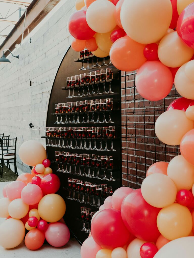 Champagne welcome wall at wedding reception with pink and orange balloon arch