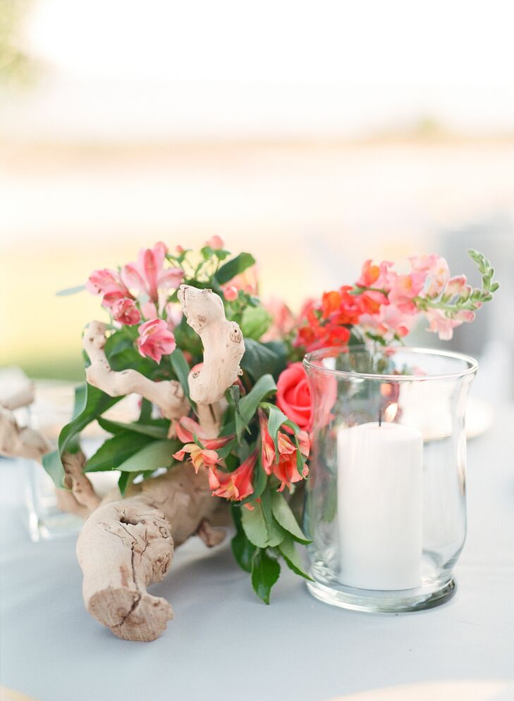 Flowers were wrapped around driftwood for a beach-themed centerpiece. The flower arrangements were