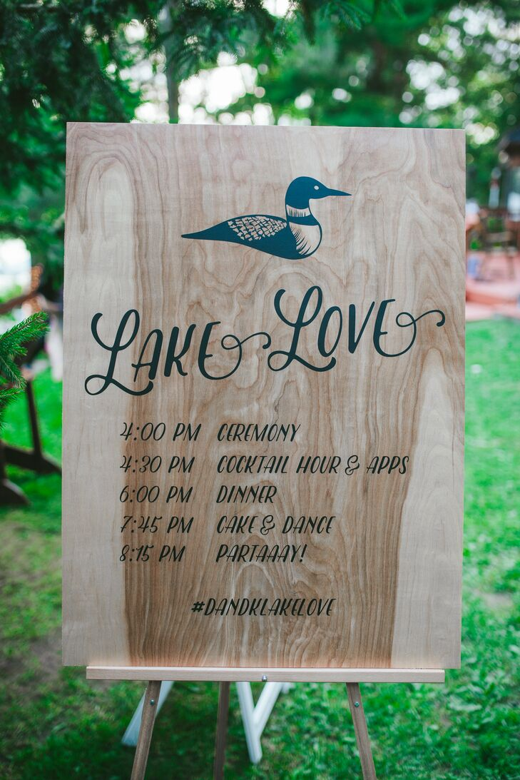 "A large wooden sign, complete with Danielle and Kyle's wedding logo (a loon) and a ""Lake Love"" header, detailed the day's lakeside wedding itinerary."