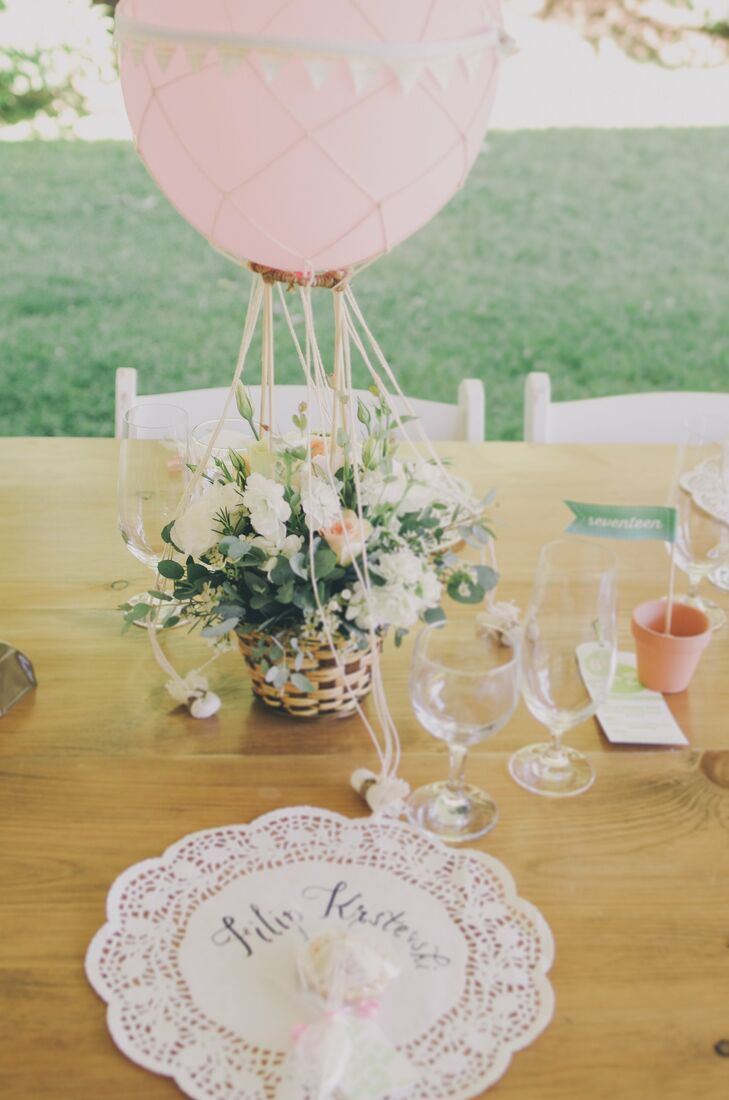 The hot air balloon inspired centerpieces were one of the bride's favorite wedding details. The romantic pastel floral arrangements, which resembled Zurry's bouquet, were all locally sourced and created by Coriander Girl. Zurry and her bridesmaids made the nets for the balloons while Brendan sewed the mini bunting flags that went around the balloons.