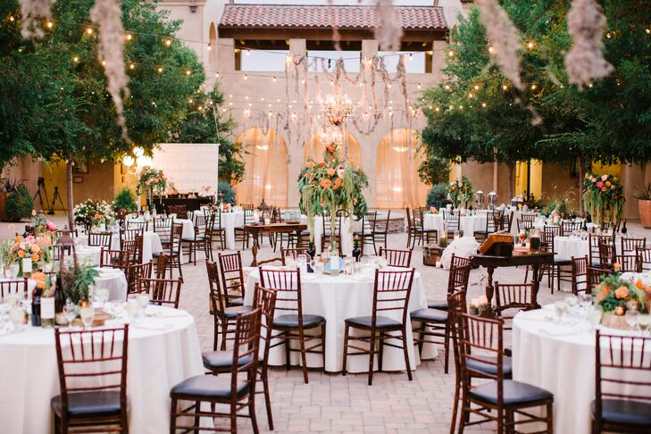 The courtyard flipped from the ceremony to the reception through round dining tables with elegant brown chiavari chairs. High and low centerpieces added pops of bright color to the table displays, arranged underneath twinkling market lights.