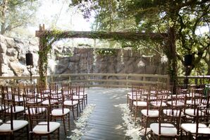 Outdoor Garden Ceremony With Hanging Floral Arrangments