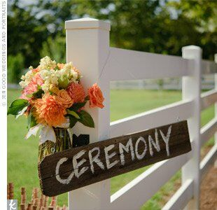 Roses, dahlias and stock adorned a wooden sign that marked the path to the ceremony site.