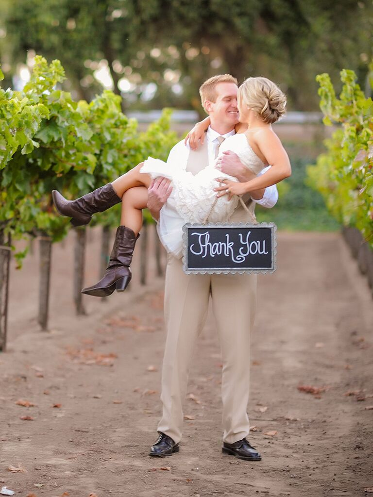 Couple wedding day pose idea with a thank-you sign