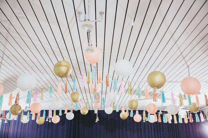 For the reception inside Ace Hotel & Swim Club in Palm Springs, California, paper lanterns and tassels decorated the white ceiling in colors of peach, gold, blue and white.