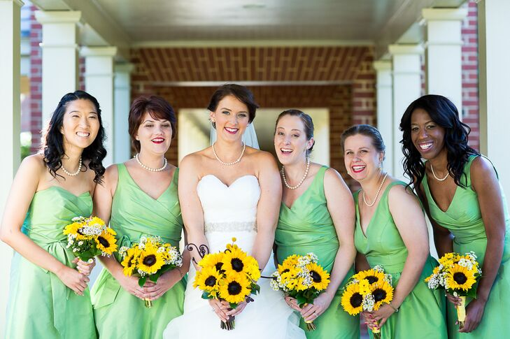 """The bridesmaids wore """"appletini"""" green dresses in different styles by Alfred Sung. They carried small bouquets of sunflowers and baby's breath."""