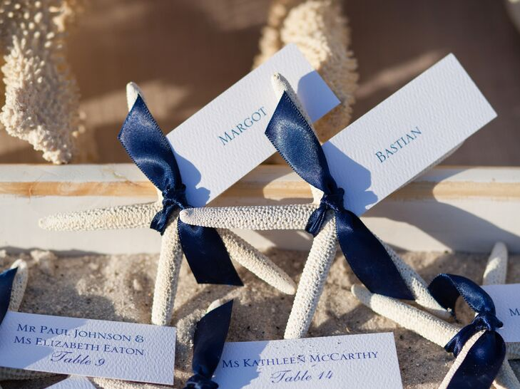 The white escort cards were tied with a navy blue ribbon to white dried starfish, adding a nautical touch to the wedding decor.
