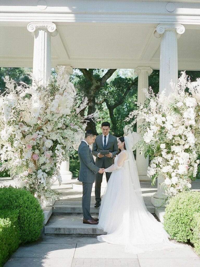 Bride and groom reciting vows in front of lavish white floral installations at summer wedding
