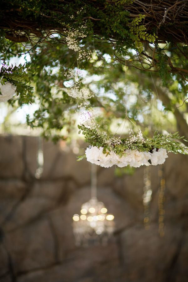 Adding warmth and elegance to the outdoor ceremony were several hanging flower arrangements with white roses, baby's breath, and peonies, as well as lit chandeliers.