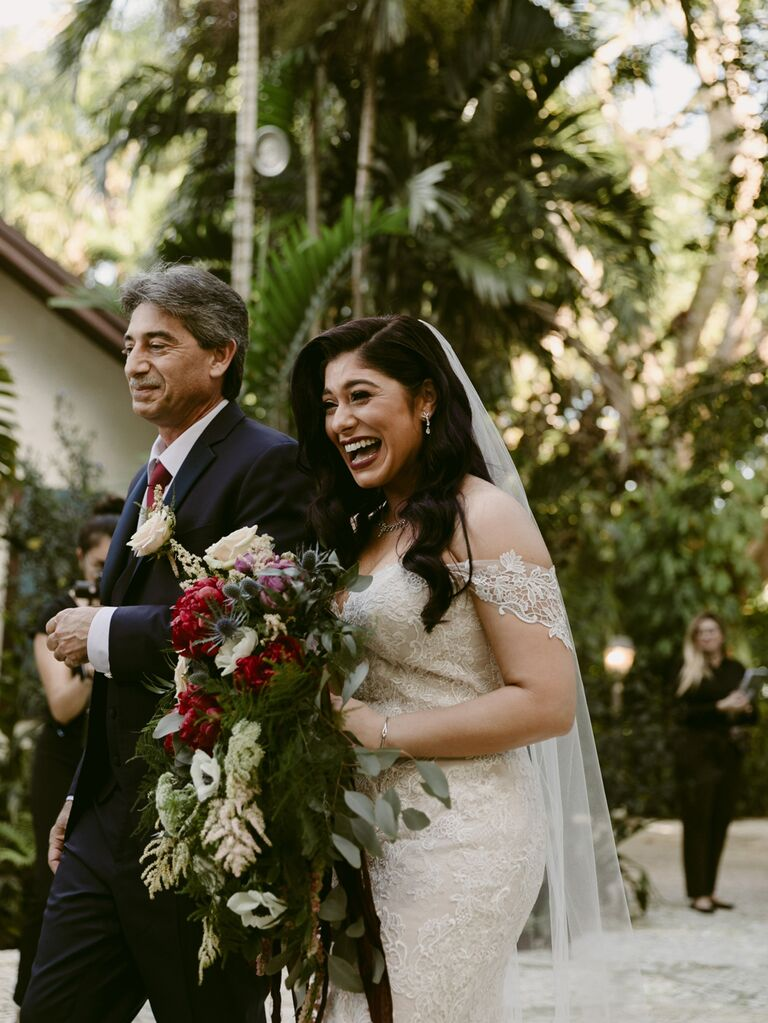 Bride walking down the aisle with father at tropical wedding ceremony