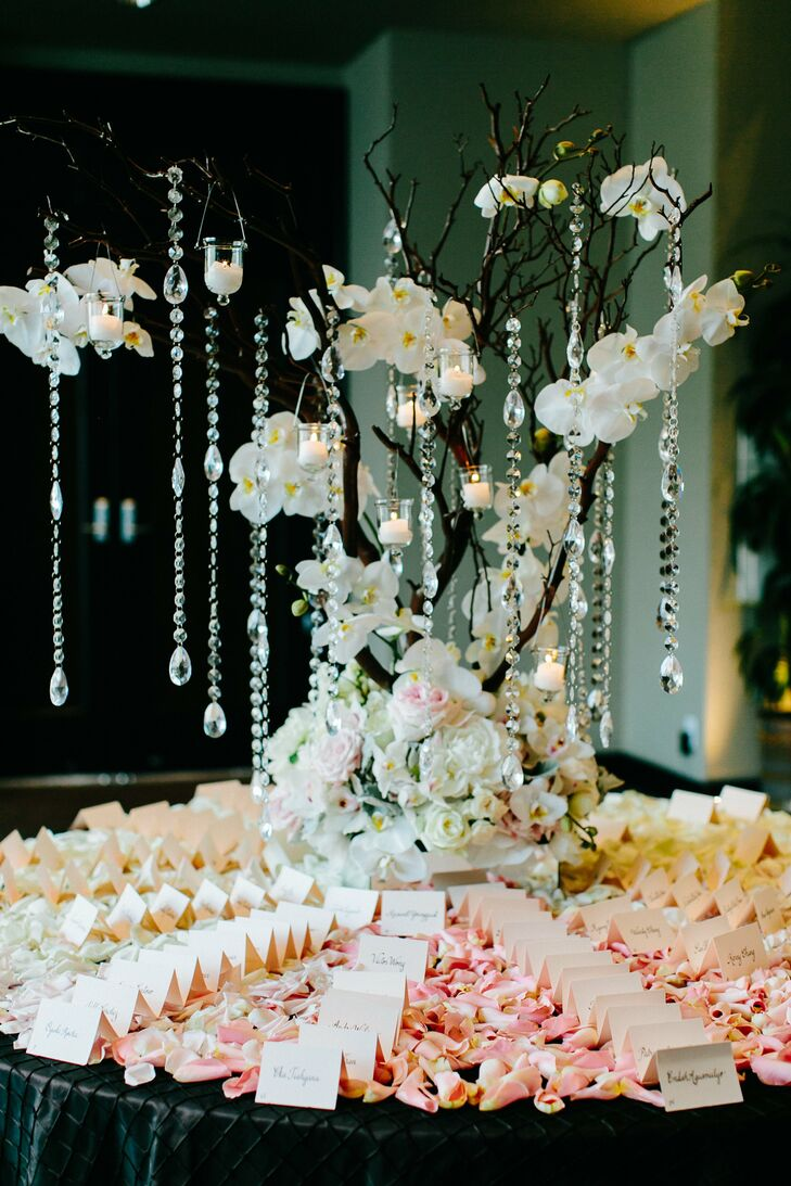 The couple's wedding planner hand wrote each escort card in calligraphy and arranged the cards on top of scattered petals and around a centerpiece of white orchids with hanging crystal garlands.