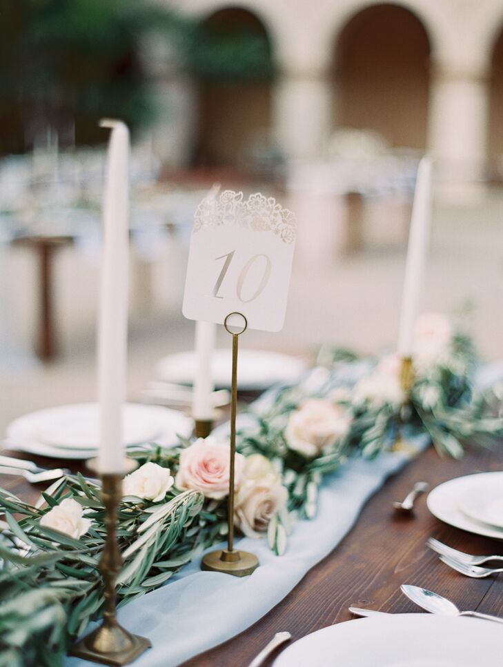 Classic white numbers on tall metal holders marked the tables. Each number stood close to the lush garland speckled with pastel flowers that draped down the middle of the dining table, in addition to tall white candles in brass candelabras.