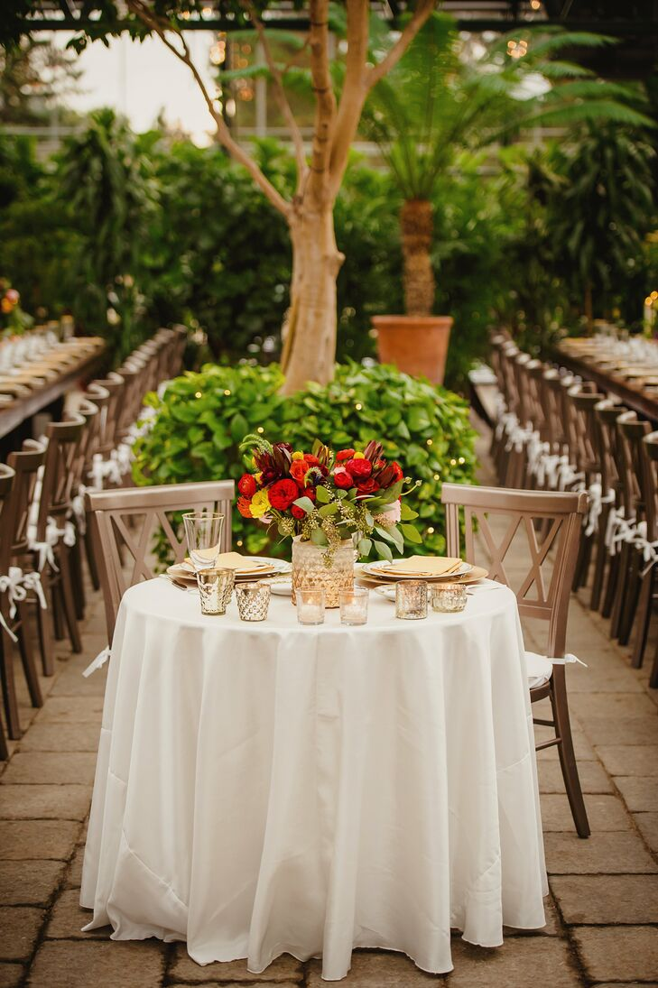 Carly and David had their own table, which they covered with simple white linens, golden place settings, mercury glass vases filled with bright red flowers and a scattering of mercury glass votive candle holders.