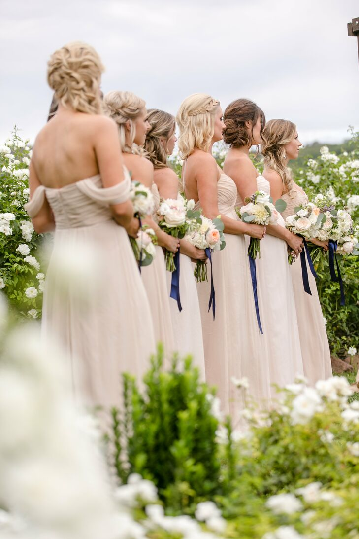 "Romantic and soft in color, Allie's bridesmaid bouquets matched their dresses. A navy ribbon hung from each stem. ""I wanted eucalyptus in them as well,"" she says. ""I love the look, and it smells wonderful."""