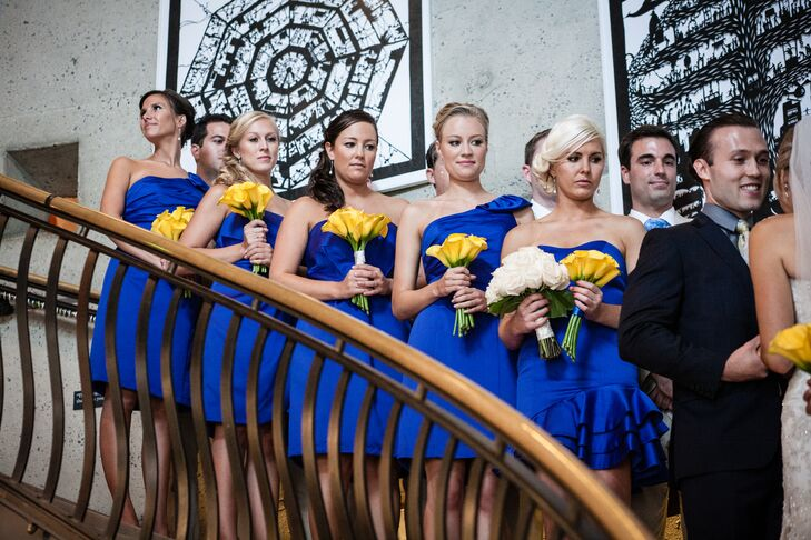 "The bridesmaids wore knee-length, cobalt blue dresses in various styles and carried yellow calla lily bouquets. ""The bouquets were simple yet stunning yellow calla lilies that held up magnificently in the heat,"" says Emily."