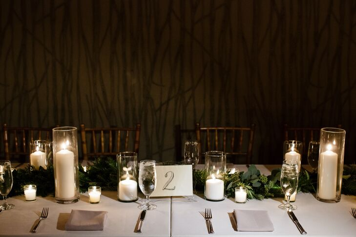 Lily and Aaron wanted every part of the reception to be filled with candlelight and greenery, so Tiffany Chalk Events and Judy Suarez, their florist, did just that. The tablescapes were lined with runners of seeded eucalyptus and leaves from evergreen trees, creating an enchanted forest-like ambience. This was enhanced with tons of candlelight that shined from glass cylinder vases.