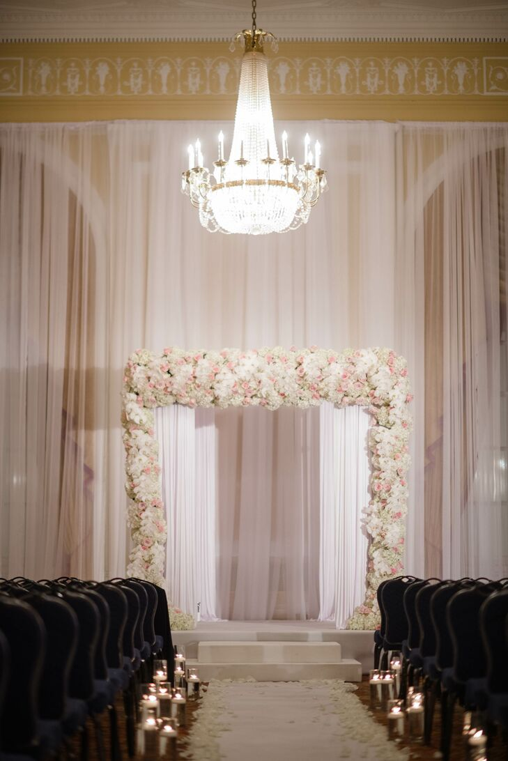 A dense floral arbor featuring fluffy hydrangeas, soft roses and phalaenopsis orchids was the focal point of the romantic ceremony space.